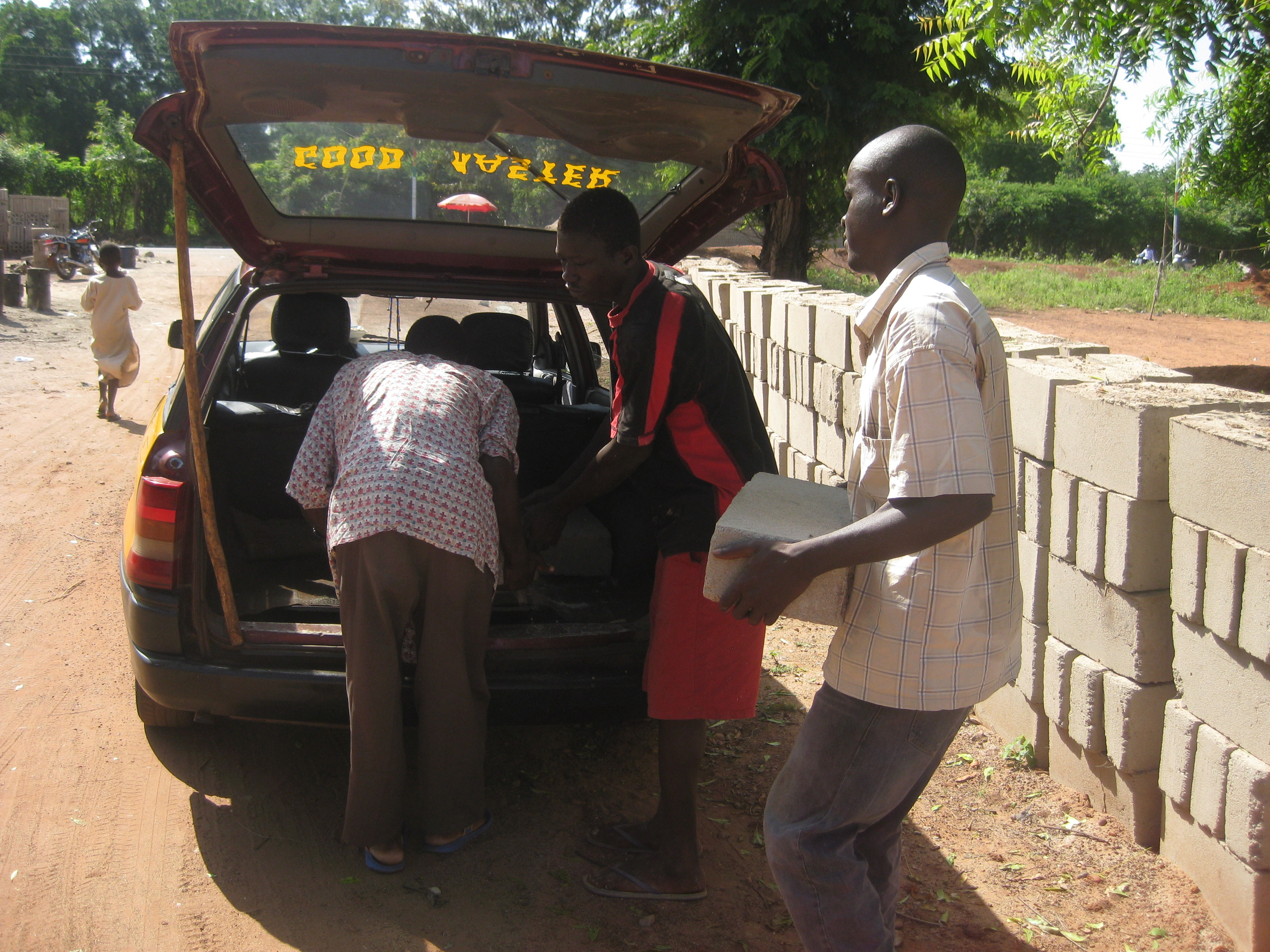 Loading up the taxi with bricks, cement, and sand to bring to Jarigu