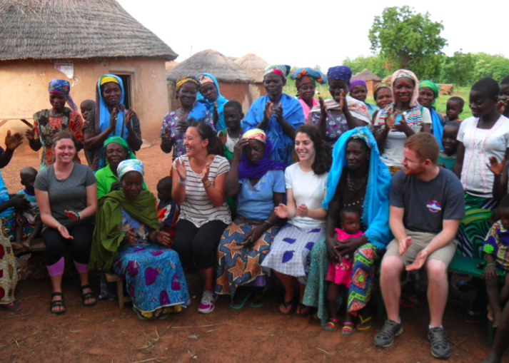 The team clapping along with the women of the village during the appreciation song.