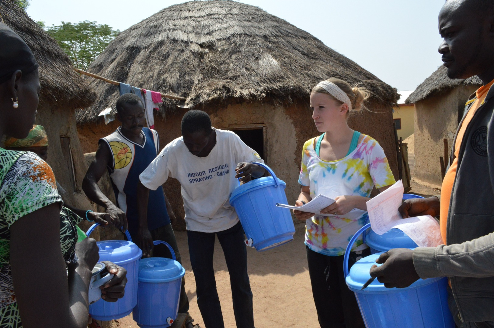 Meaghan distributing safe storage containers with the help of some village members