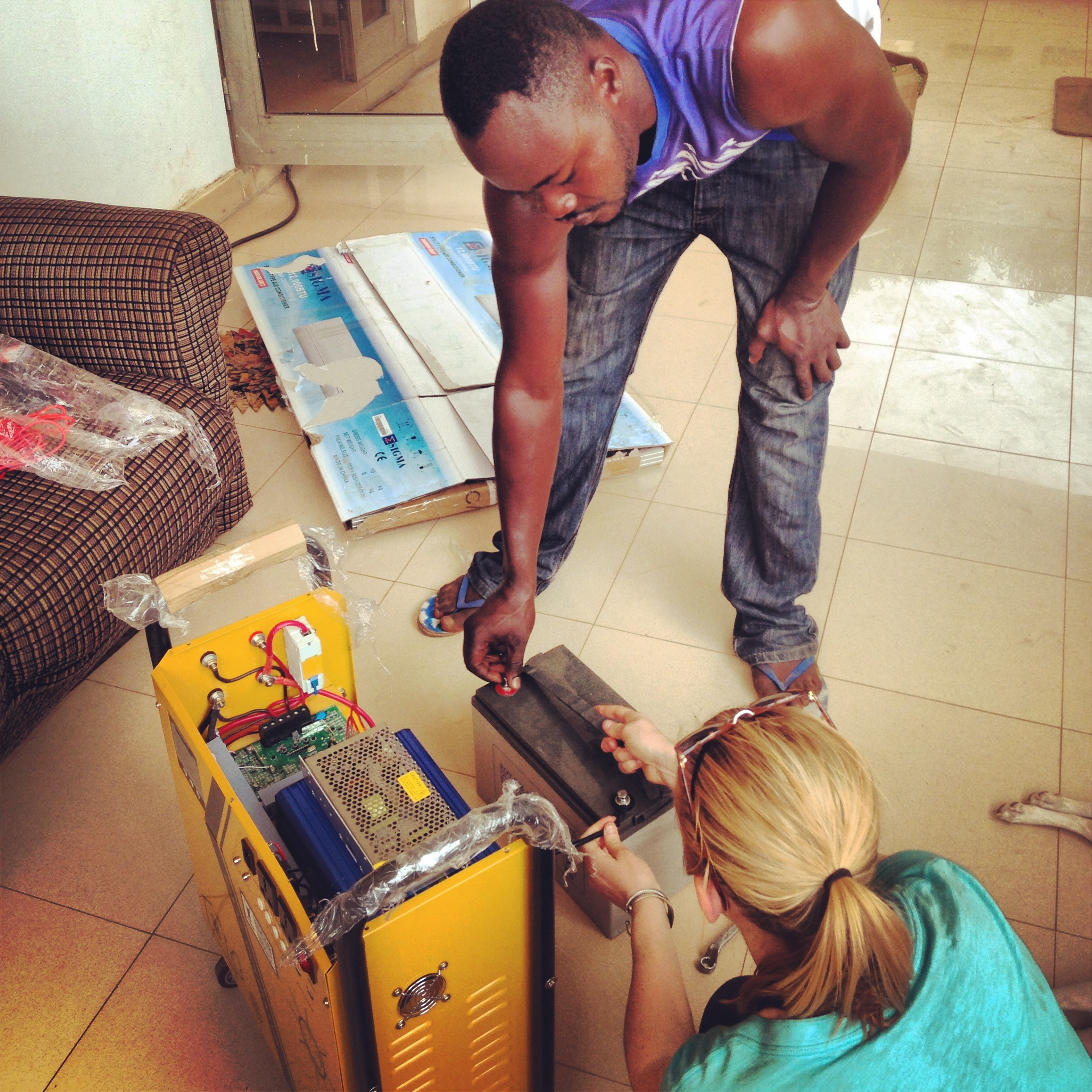 Shak teaching Sam how to connect the battery to the inverter.