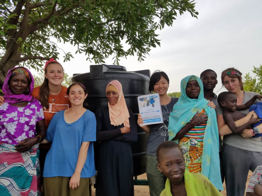 The team and new entrepreneurs pose at the water center.