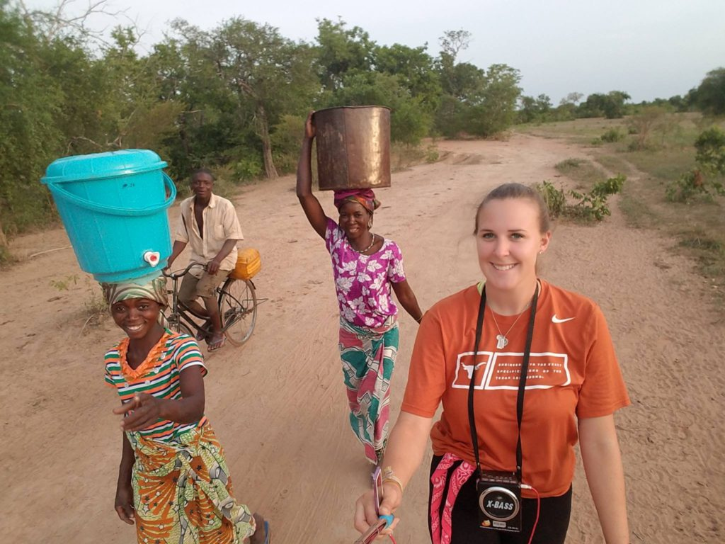 Savannah walks back from the dugout and water center after a successful opening day with Mahamuyili community members.