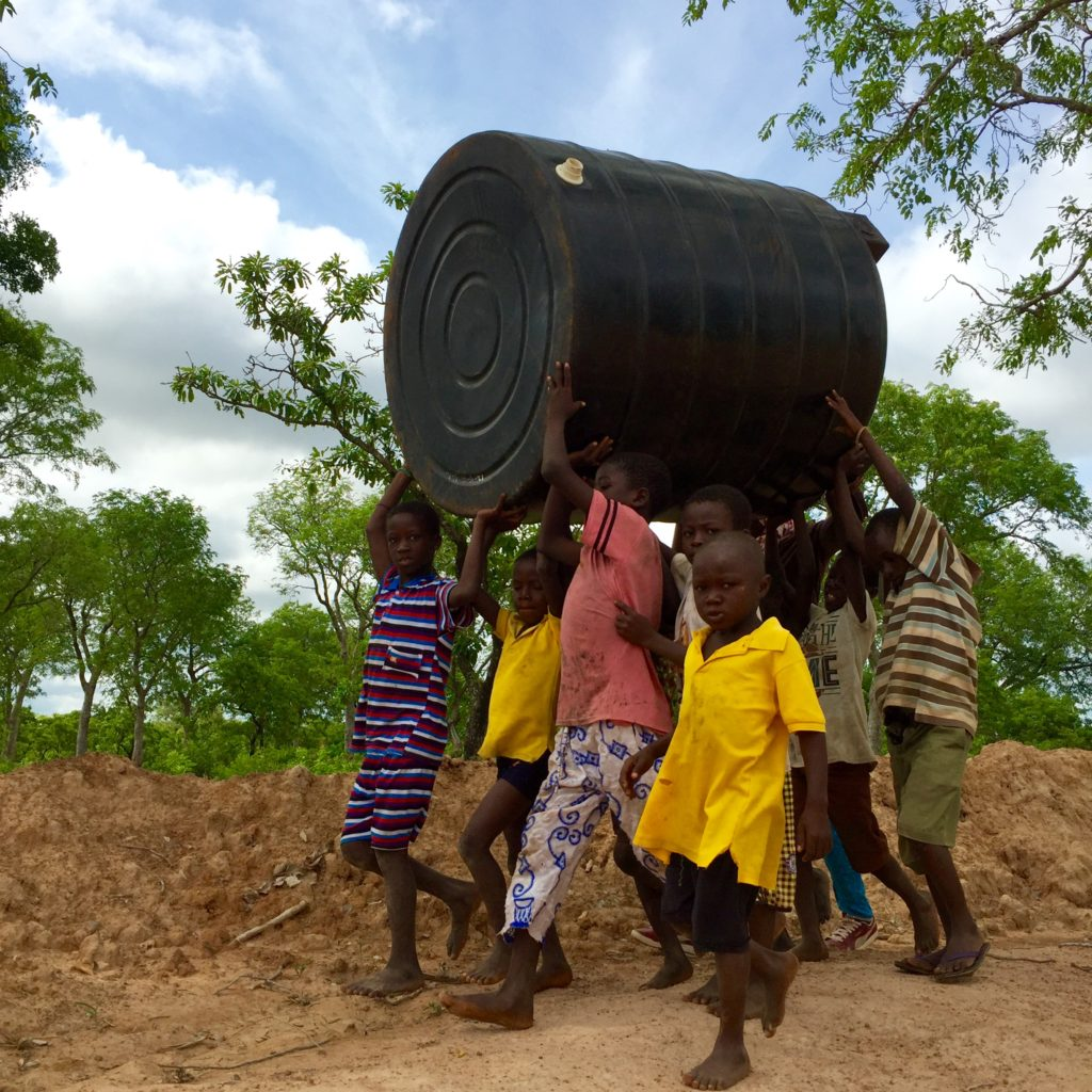 Kanjeyili kids help carry the polytank.