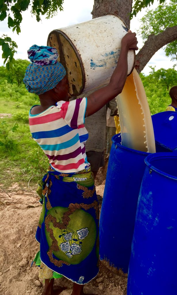 One of the new entrepreneurs from Kanjeyili fills a blue drum to get ready for alum treatment.