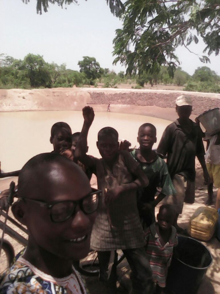 The community of Vogyili reinforces their dugout in the hope that it will hold more water this rainy season (background). In the foreground, kids pose with Eric